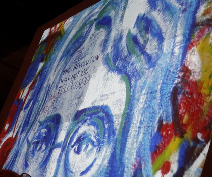 """This wonderful digital projection of artwork states (in the middle of John Lennon's forehead) """"the revolution will never be televised."""""""